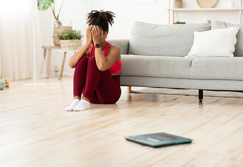 Desesperada niña africana sentada cerca de balanzas llorando después de pesar en interiores
