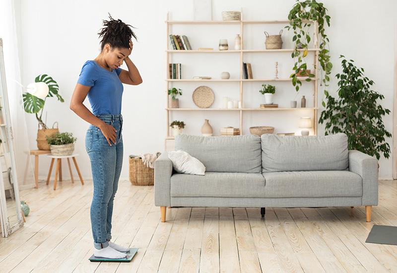 Feliz chica africana pesando a sí misma de pie en balanzas de peso en casa