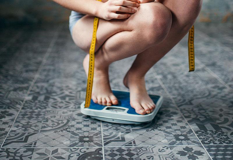 Mujer delgada en ropa interior pesaba en una escala