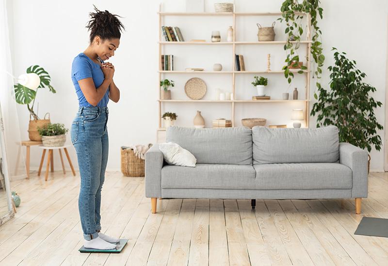 Triste niña africana de pie en balanzas pesando a sí misma en casa